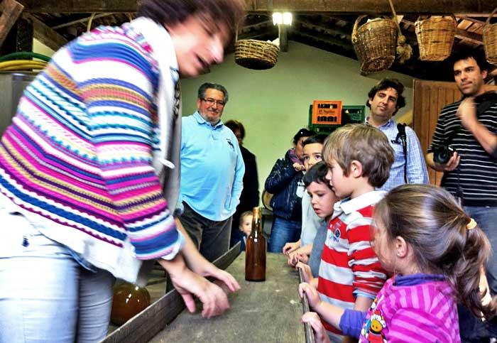Los niños escuchan atentamente el proceso de elaboración de la sidra