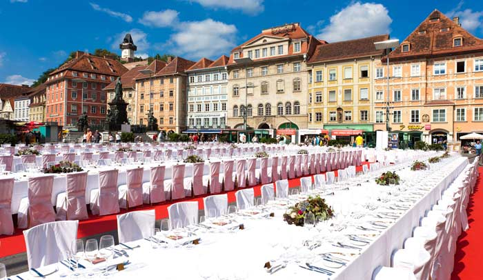 Más de 700 personas se sientan a la mesa con cubiertos magníficos para degustar las mejores obras culinarias y los mejores vinos del país en un escenario fabuloso ante el monte Schlossberg, la torre Uhrturm y el ayuntamiento / Foto Turismo Graz