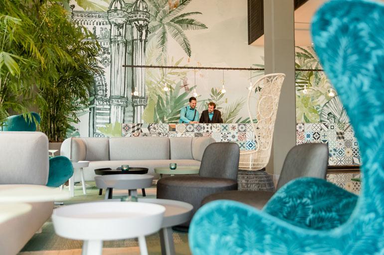 Recepción del Motel One Barcelona Ciutadella. El azul turquesa es el color corporativo del hotel y está presente en el uniforme del personal