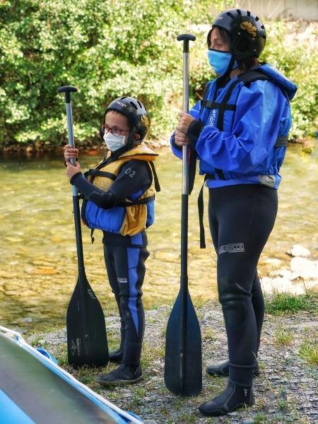 Madre e hijo prestando atención a las instrucciones del monitor de rafting